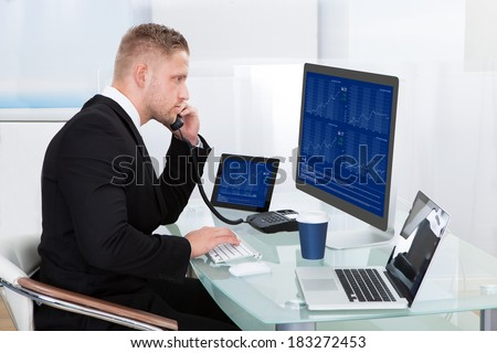 Hardworking businessman at his desk working on the computer screens simultaneously as he takes a call on his mobile phone