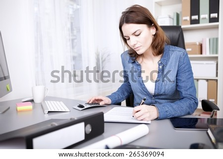 Hardworking businesswoman sitting at her desk in the office writing a report and doing calculations on a manual calculator - stock photo