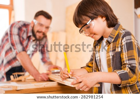 Hardworking is a key to success. Smiling little boymaking measurements on the wooden plank while working with his father in workshop  - stock photo