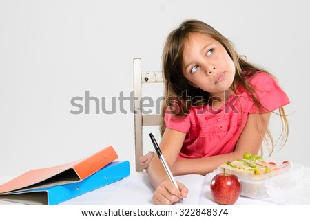 Hardworking school girl thinks and concentrates on her homework with an apple and healthy packed lunch on the table - stock photo