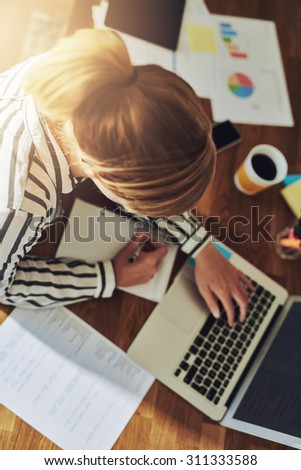 Hardworking successful female entrepreneur working at her desk in her home office writing notes as she researches new markets on the computer, overhead view - stock photo