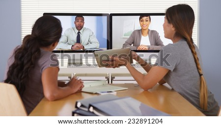 Hardworking team of diverse business colleagues having a video conference - stock photo