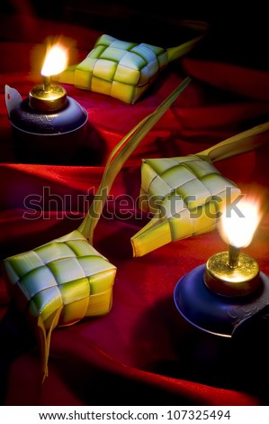 Hari Raya Aidilfitri (Eidul Fitri) decoration featuring the famous ketupat and panjut lamp in its original ambient lighting at night. - stock photo