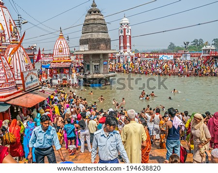 HARIDWAR, INDIA - APRIL 15, 2010: People performing a religious ritual on Main bathing Ghat in the holy river Ganga at the Kumbh Mela. Haridwar is regarded as one of the seven holiest places to Hindus - stock photo