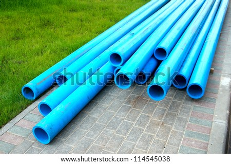 Harmless polyethylene water pipes on a green grass - stock photo