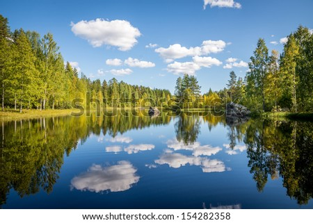harmonious picture of a tranquil lake with reflections of trees and sky - stock photo