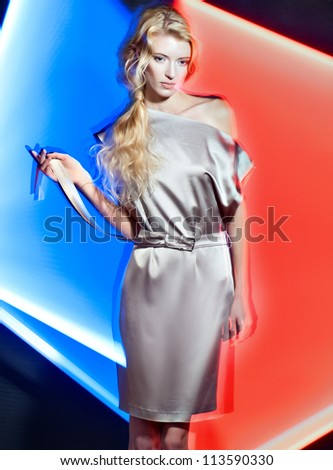 harmonous fashion blond women poses in fashionable clothes on a color background - stock photo