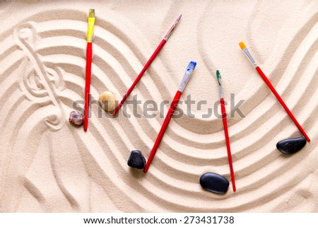 Harmony and music at the beach with an artistic conceptual image of a wavy score drawn in golden sand with a treble clef and musical notes of smooth pebbles and kids paintbrushes - stock photo