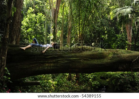 harmony in nature: woman relaxing on a fallen tree trunk in a tropical forest