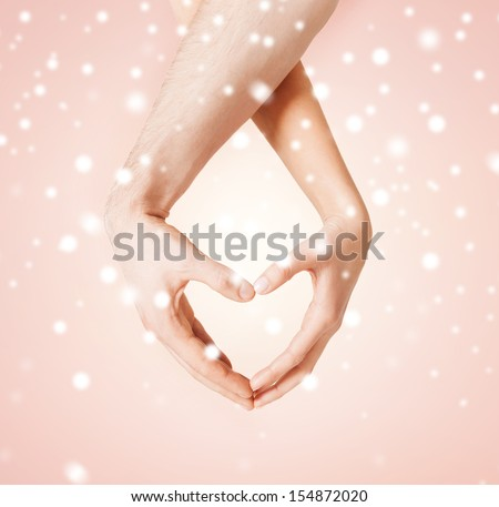 harmony, love, family and charity concept - woman and man hands showing heart shape - stock photo