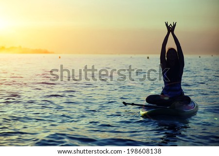 Harmony with the nature in yoga meditation, silhouette of a girl doing sup yoga at the beautiful orange sunset - stock photo