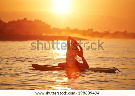 Harmony with the nature in yoga meditation, silhouette of a girl doing sup yoga at the beautiful orange sunset reflected on the sea - stock photo