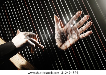 Harp strings closeup hands. Harpist with Classical Music Instrument - stock photo