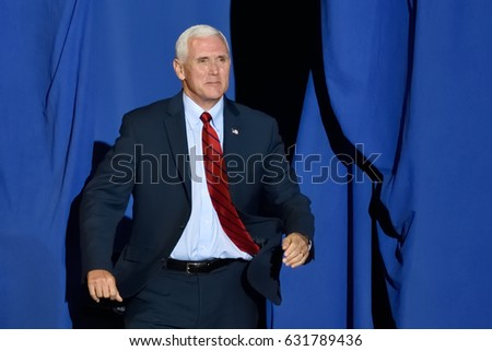 "HARRISBURG, PA - APRIL 29, 2017: Vice President Mike Pence ""bursts"" through the opening on stage at a Trump campaign rally marking 100 days in office. Held at the Farm Show Complex and Expo Center."
