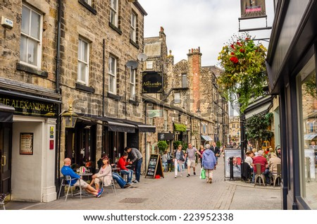 Harrogate, UK - September 27, 2014: People enjoying a warm Autumn day in a cobbled Street lined with Restaurant and Shops. Harrogate is consistently voted as one of the best places to live in the UK. - stock photo