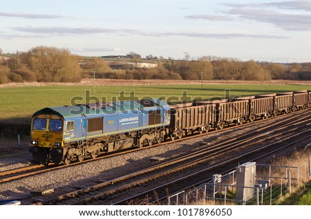 HARROWDEN, UK - MARCH 7: A Freightliner operated class 66 diesel locomotive hauls a rake of spoil wagons towards the open cast site for disposal on March 7, 2014 in Harrowden