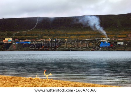 Harsh landscape with Russian city Barentsburg under the dark barren mountain - view from another shore with deer bones and horns at foreground in Spitsbergen (Svalbard island), Norway, Greenland sea - stock photo