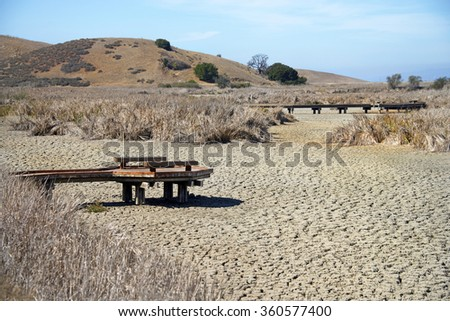 Harsh weather drought conditions in Northern California, dried up lake bed with pier jetty out over the cracked earth with harsh sunlight heating up the landscape, dead grass background Coyote Hills - stock photo