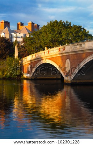 Harvard University bridge over the Charles River between Cambridge and Boston with beautiful reflections on the water below.  Copy space - stock photo