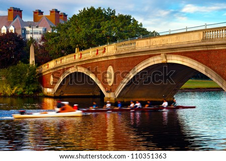Harvard University crew team in a scull going under the Weeks Bridge on the Charles River.  Beautiful golden morning light and reflections on the water.
