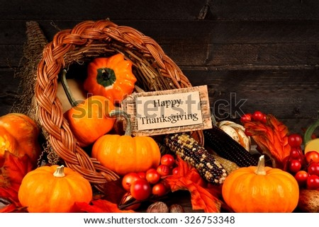 Harvest cornucopia close up with Happy Thanksgiving gift tag on dark wood background - stock photo
