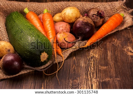 Harvest fest. Fresh organic vegetables: carrot, potato, sugar beet and vegetable marrow on rustic wooden background. Selective focus. Toned image - stock photo