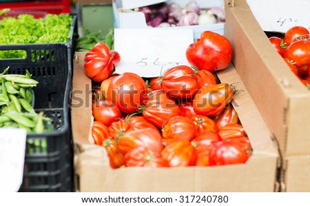 harvest, food, vegetable and agriculture concept - close up of oxheart tomatoes in box at street market - stock photo