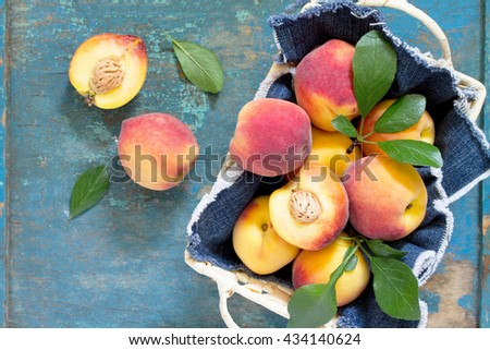 Harvest fresh ripe peaches in a wicker basket on the vintage wooden table, top view. Space for your text. - stock photo