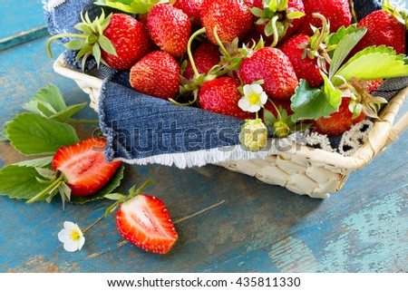 Harvest of fresh ripe strawberries in a wicker basket on old wooden table, selective focus. - stock photo