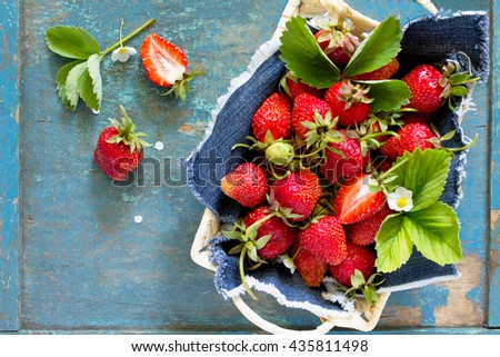 Harvest of fresh ripe strawberries in a wicker basket on old wooden table, top view. - stock photo