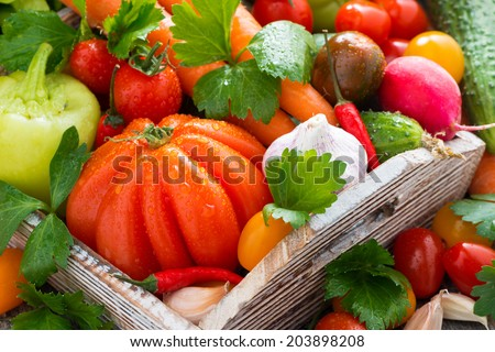 harvest of fresh seasonal vegetables in a wooden box, close-up, vertical