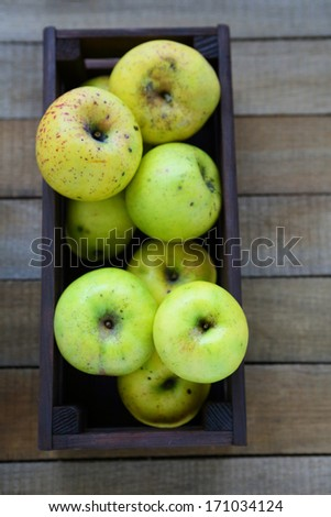 harvest of green apples in wooden crate, top view - stock photo