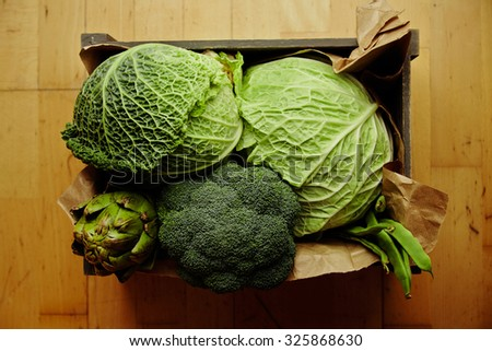 Harvest of vegetables in wooden box with craft paper top view - stock photo