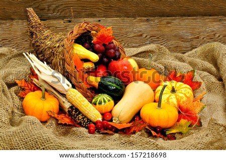 Harvest or Thanksgiving cornucopia filled with vegetables on a burlap and wood background - stock photo