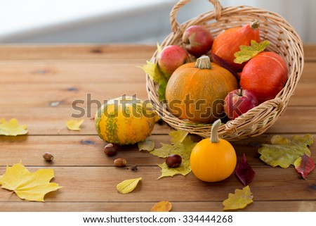 harvest, season, advertisement and autumn concept - close up of pumpkins in wicker basket with leaves on wooden table at home - stock photo