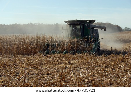 Harvester finishing corn field stirring up dust - stock photo