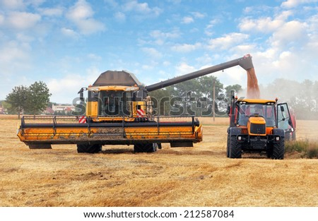 Harvester machine and tractor at harvest - stock photo