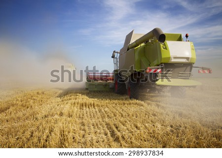 Harvester moving on the field producing big cloud of dust  - stock photo