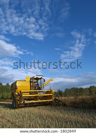 Harvester-thresher rests after work, at sunset - stock photo