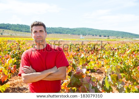 Harvester winemaker farmer proud of his vineyard in autumn golden red leaves at Mediterranean - stock photo