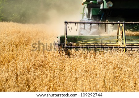 Harvesting machine in wheat crops - stock photo
