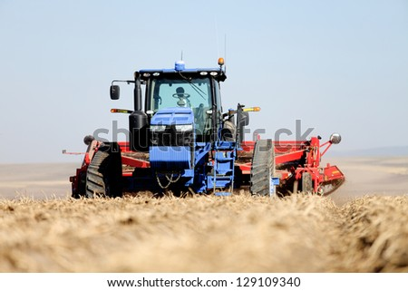 Harvesting machinery working in a potato field - stock photo