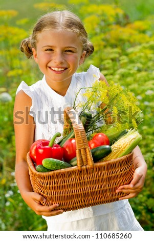 Harvests of vegetables - lovely girl with the basket of ecological harvests - stock photo