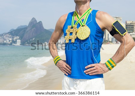 Hashtag gold medal athlete wearing mobile phone technology armband stands listening to motivational music outdoors on Ipanema Beach Rio de Janeiro Brazil  - stock photo