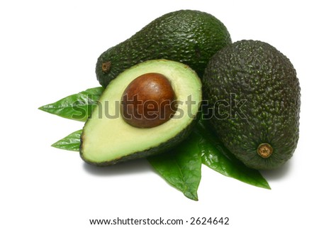 Hass Avocados, two whole, one halved, with young leaves from an  Avocado tree, isolated on white - stock photo