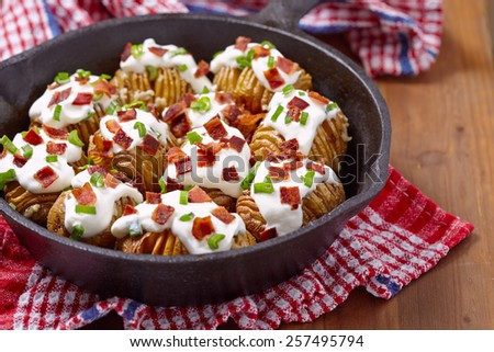 Hasselback potatoes with cheese, sour cream, bacon and green onion - stock photo