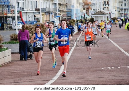 HASTINGS, ENGLAND - MARCH 23, 2014: Young people take part in the 24th annual Hastings Mini Run on the seafront. The 2.5km race for 11-16 year olds is held in conjunction with the Half Marathon race. - stock photo