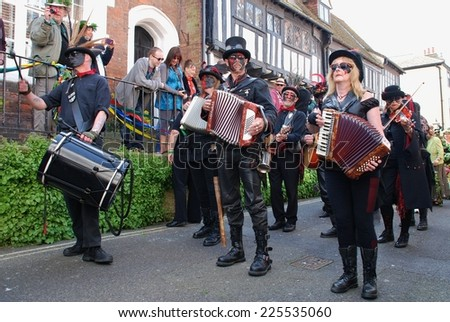 HASTINGS, ENGLAND - MAY 5, 2014: Black faced musicians perform at the parade through the Old Town during the annual Jack In The Green festival. The event is held on the May Day public holiday. - stock photo