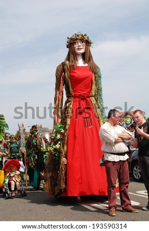 HASTINGS, ENGLAND - MAY 5, 2014: Flora the Singleton Giant is paraded on the West Hill during the annual, May Day, Jack In The Green festival. Pageant Giants are a centuries old tradition in Britain. - stock photo