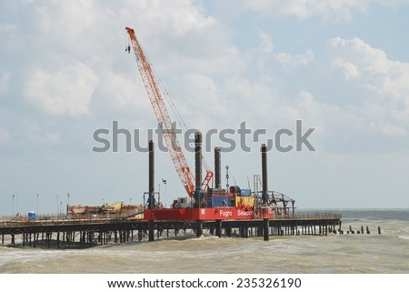 HASTINGS, ENGLAND - NOVEMBER 9, 2014: A 36mtr high crane mounted on a Fugro Seacore jackup barge takes part in the rebuilding of the Victorian pier. The pier was badly damaged by fire in October 2010. - stock photo
